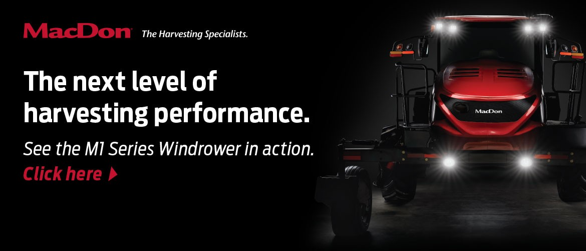 MacDon M1 Series Windrower on black background with bright lights