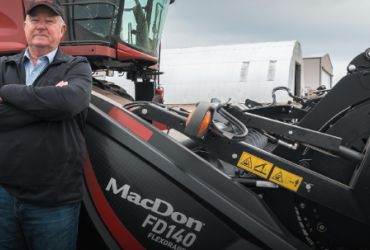 Tim Demaray, owner of Demaray Harvesting standing in front of MacDon FD140 FlexDraper®