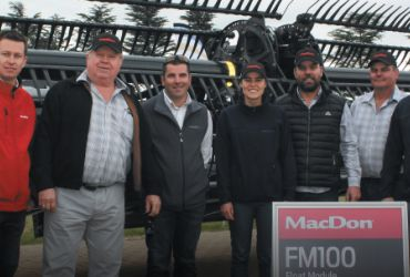 South African Vitamech employees standing in front of a MacDon FlexDraper.